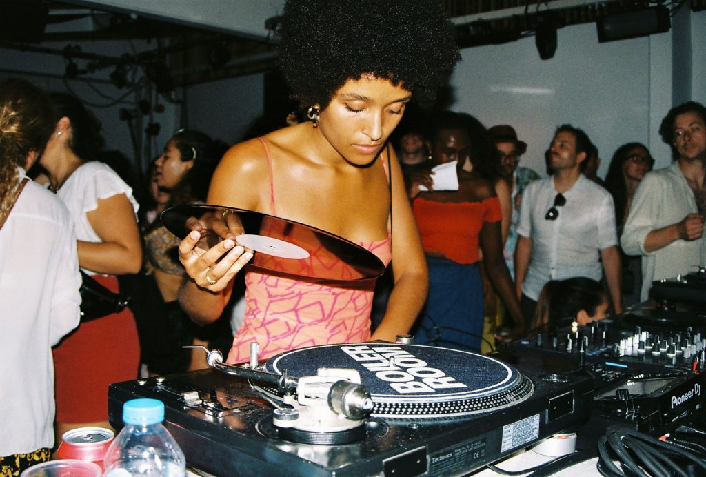 Zakia Sewell at a DJ deck during a party