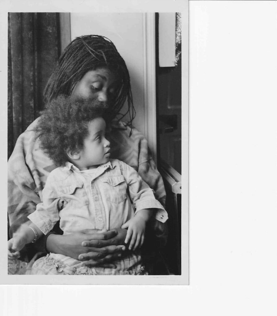 A black and white photo of Zakia Sewell at a young age, being held by her mother