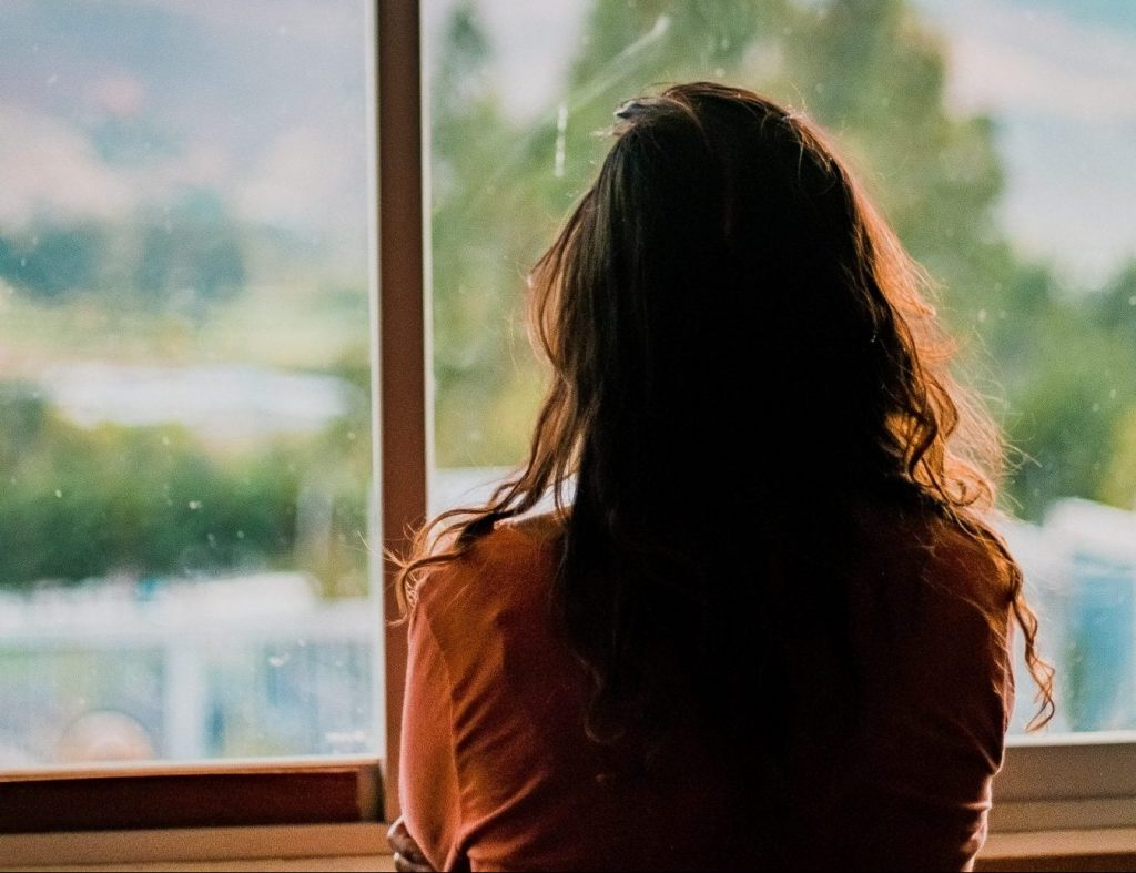 Woman with long brown hair looking out of the window