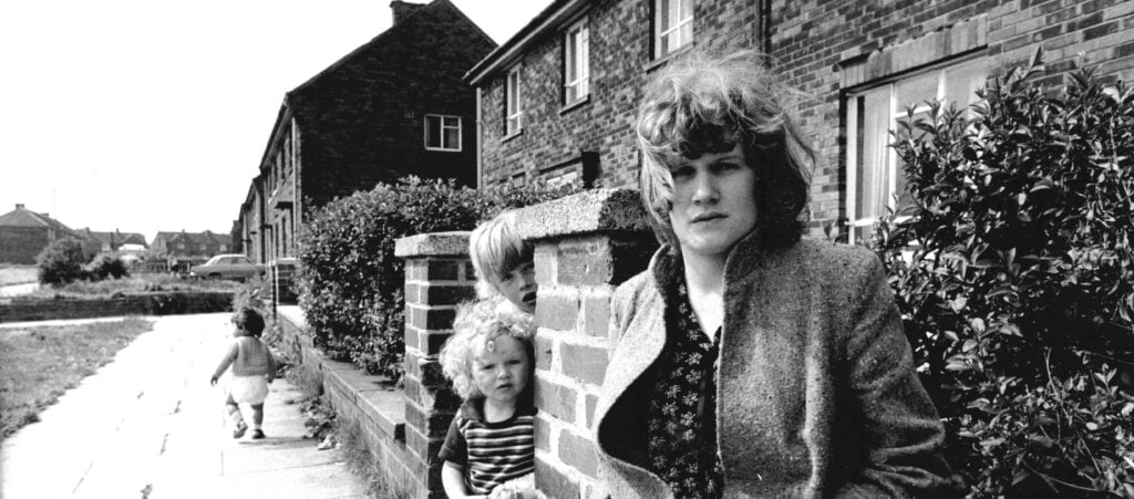Andrea Dunbar, black and white photo of a woman with hair down to her shoulders, outside a house with two children running around behind her.