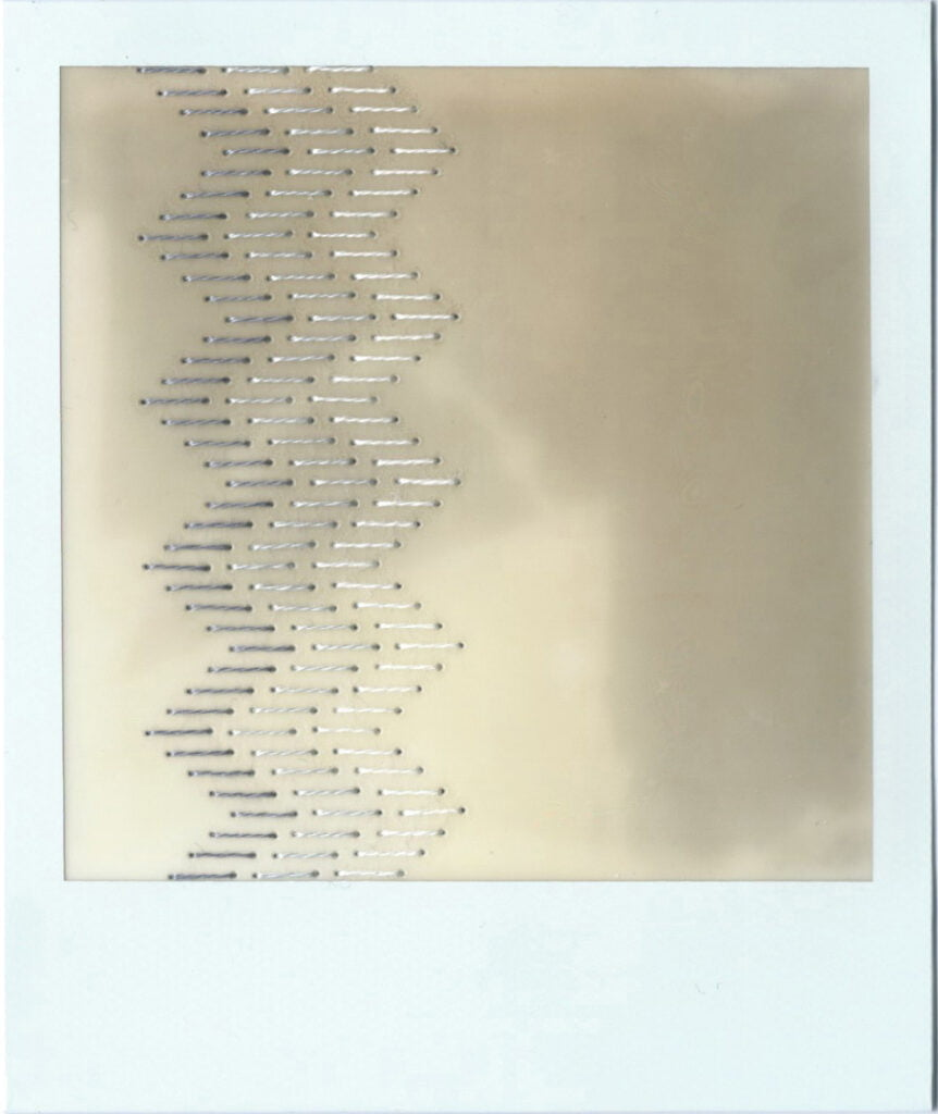 The image is a polaroid, blur of grey and white, a vague imprint of the shadows of some blinds that they sat below on a windowsill. There is a traditional blackwork embroidery pattern stitched down the left hand side of the polaroid. The stitching is done in gradients of grey. On the first photo, the pattern consists of rows of staggered straight lines that give the overall impression of a column of zig zags.