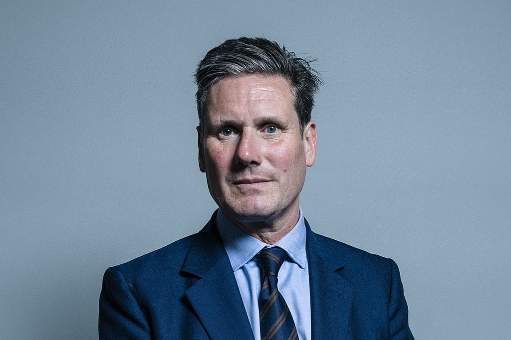 Portrait of Keir Starmer with swept up grey hair, in a blue suit and stripy tie.