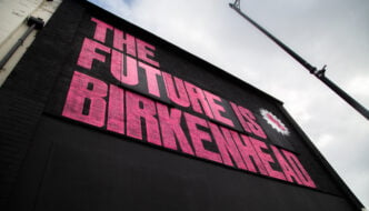 Pink writing the future is birkenhead on black background, on an outside wall