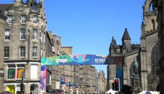 View of Edinburgh street during the festival, with large colourful banner saying 'Fringe' and crowd of people below it