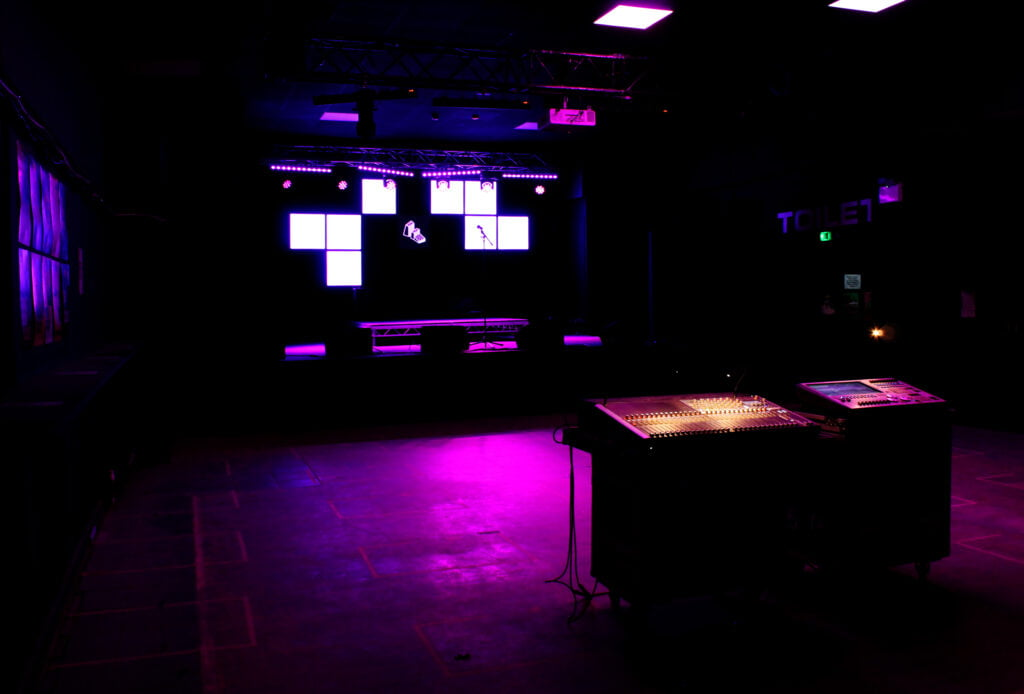 Dark interior with purple light on the floor, coming from a stage visible in the background