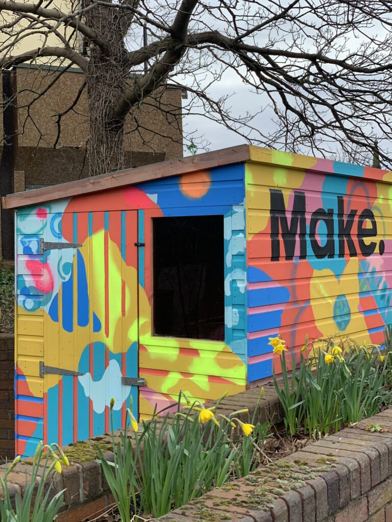 Brightly coloured painted shed with floral motifs and the word 'Make.' painted on the right hand side. Daffodils in the foreground and a leafless tree in the background.