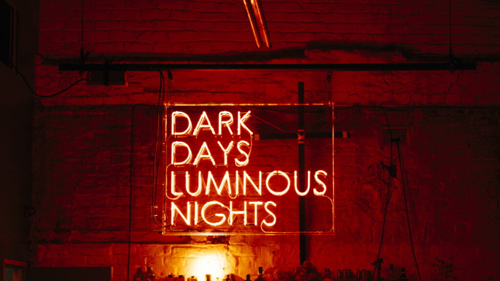 A red neon sign with the words 'DARK DAYS LUMINOUS NIGHTS' against a brick wall.