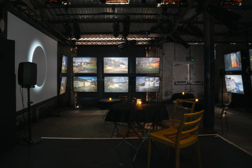 Dark room with a large screen on the left and smaller lightboxes in the centre, where photographs of Manchester are displayed. There are tables in front of it, with black tablecloth, candles and chairs around it.