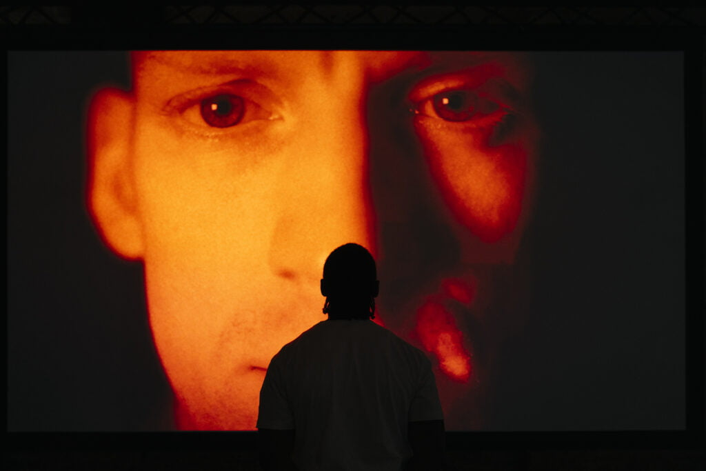 Face of a man on a large screen, lit up by red light. There is a silhouette of a man in front of it, with his back to the camera.