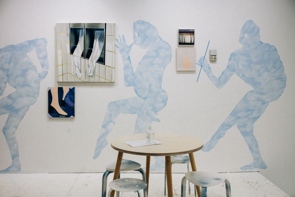 Pale blue paintings of strange human-like creatures on a wall, next to rectangular canvases depcting a window, feet and a curtain. In front of the wall there is a round wooden table and stools.