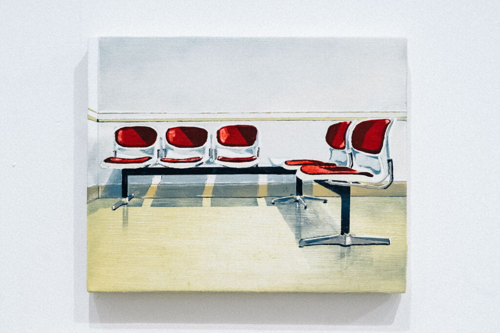 A painting by Richard Baker of a row of seats, similar to what you would find in a waiting room, side by side, joined by a metal frame, with red seats and backrests on each seat, in white casing. The floor is pale yellow and the wall behind them is white.