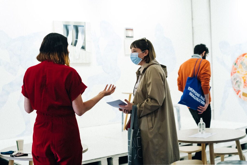 Two women talking in the exhibition space, one is wearing a red boiler suit and has shoulder length dark hair wtih blonde ends and the other is wearing a sand-coloured coat with a hood and a medical facemask. There is a man looking at the art in the background, wearing an orange jumper and holding a blue tote bag with the words 'Everyone has imagination'.