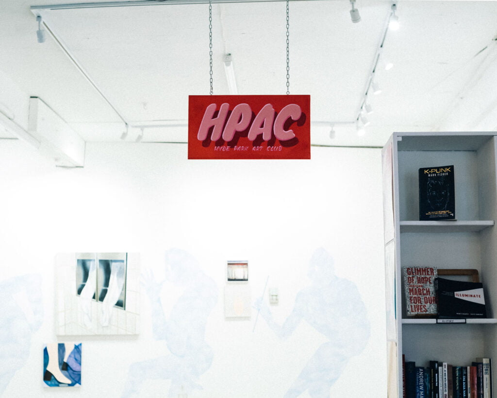 Sign of the Hyde Park Book Club in pink letters on red background, suspended from the ceiling of a white room