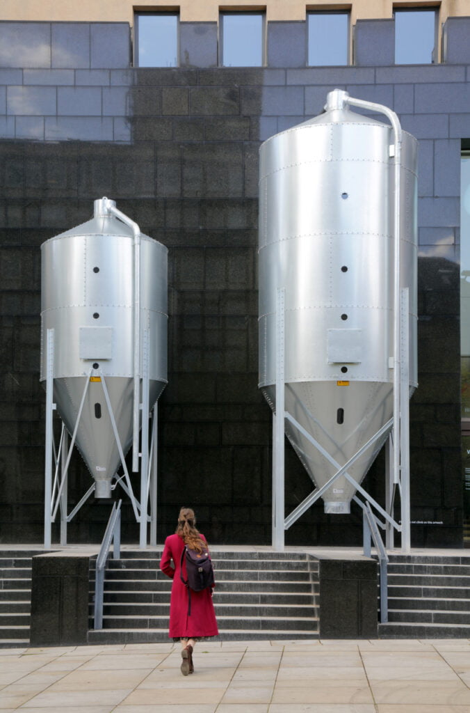 Two large silver grain silos in front of a reflective, black wall at the front of a building. At the bottom, we see the back of a woman, with long brown hair, in a raspberry pink coat, walking towards them.