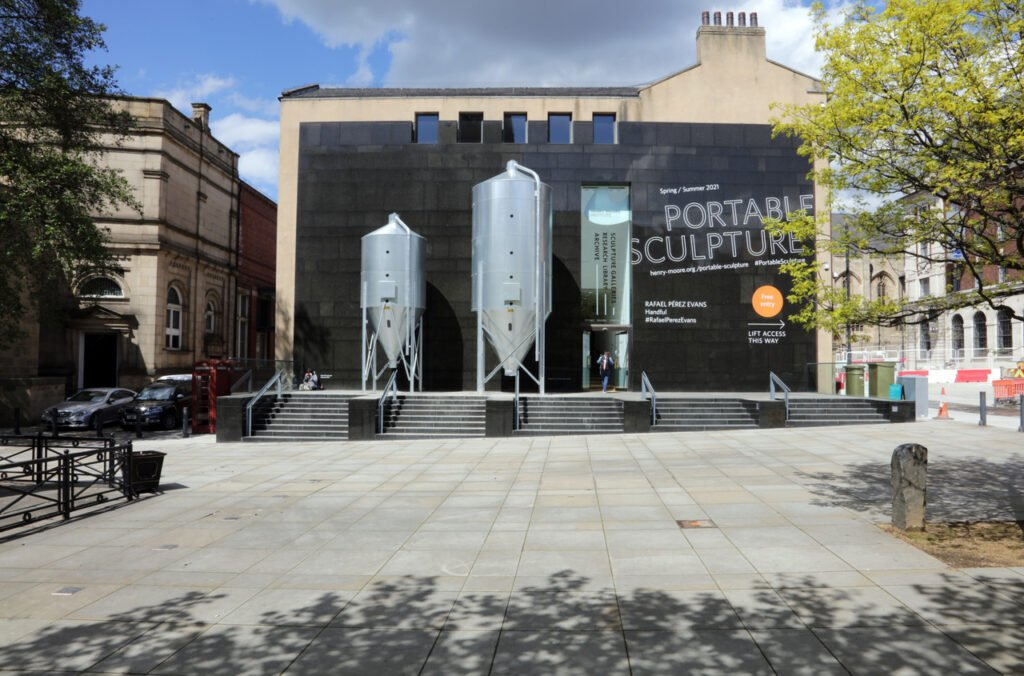 The front of the Henry More institute with a big black wall with the words 'Portable Sculpture' in big letters, next to two large, silver grain silos on silver legs. Below is a concrete staircase and a green tree on the right, in the sun.