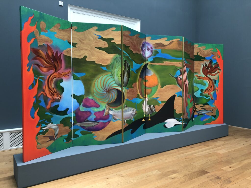 A multi-panel painting depicting land and water, the planet and animals: an orca, seagull, fish and objects like a conch and and a cabbage. The painting is a concertina shape and is standing on a small grey plinth.