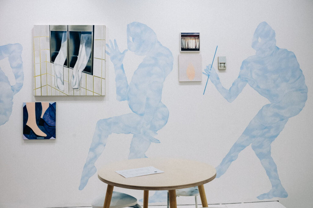 Blue figures painted on the wall with canvases next to them and a table in front of the wall.