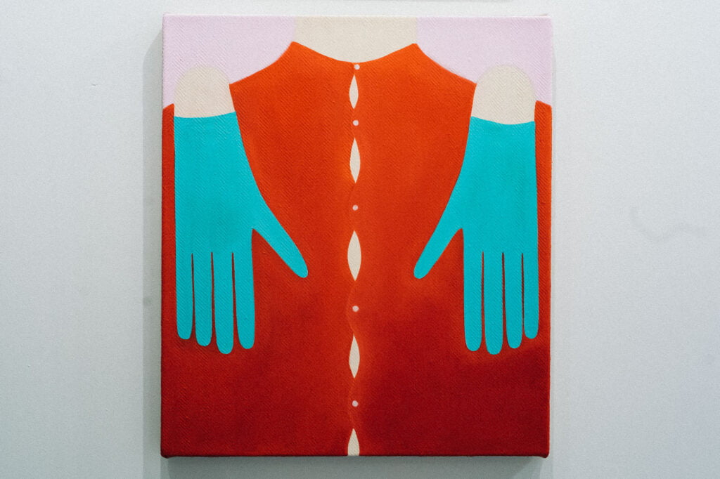 A painting of a red shirt with buttons and two hands in turquoise gloves over the shoulders, touching the chest from above.