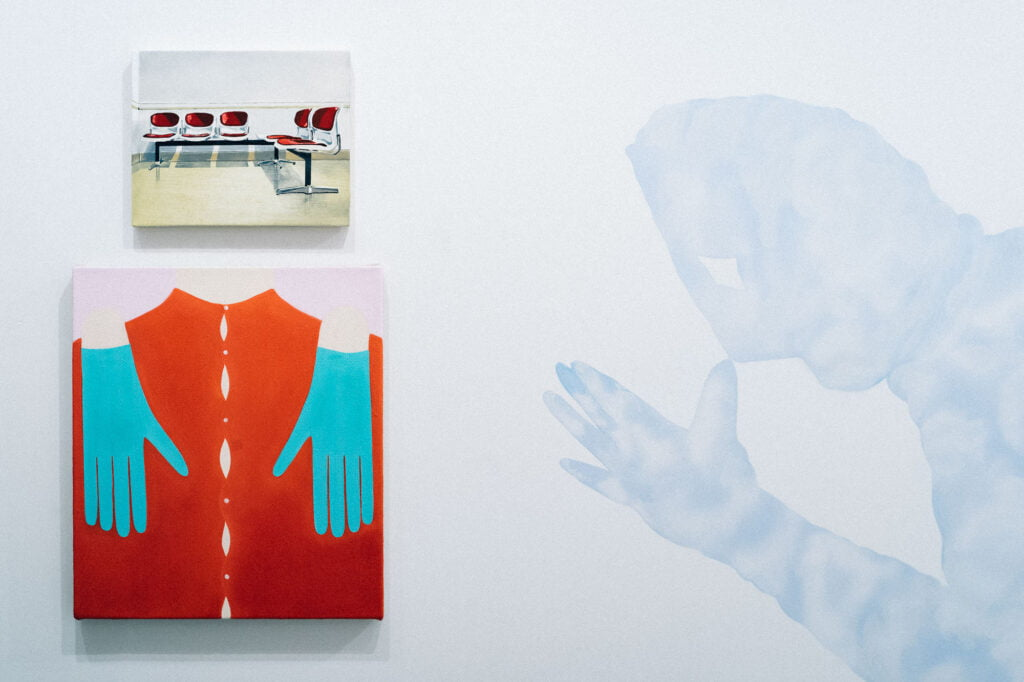 Painting of set of waiting room chairs at the top, below a painting of a red shirt with turquoise gloves on the chest, and to the right a blue figure painted directly on the wall