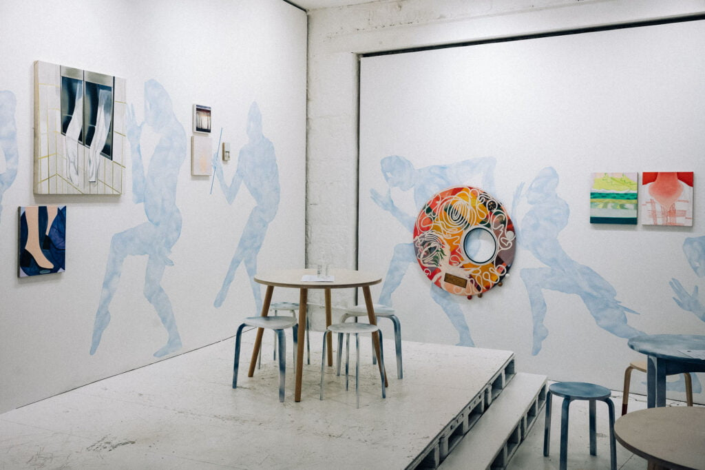 Cornern of a room with blue figures on the wall, surrounded by painted canvases, with a stage and white tables and stools in front.