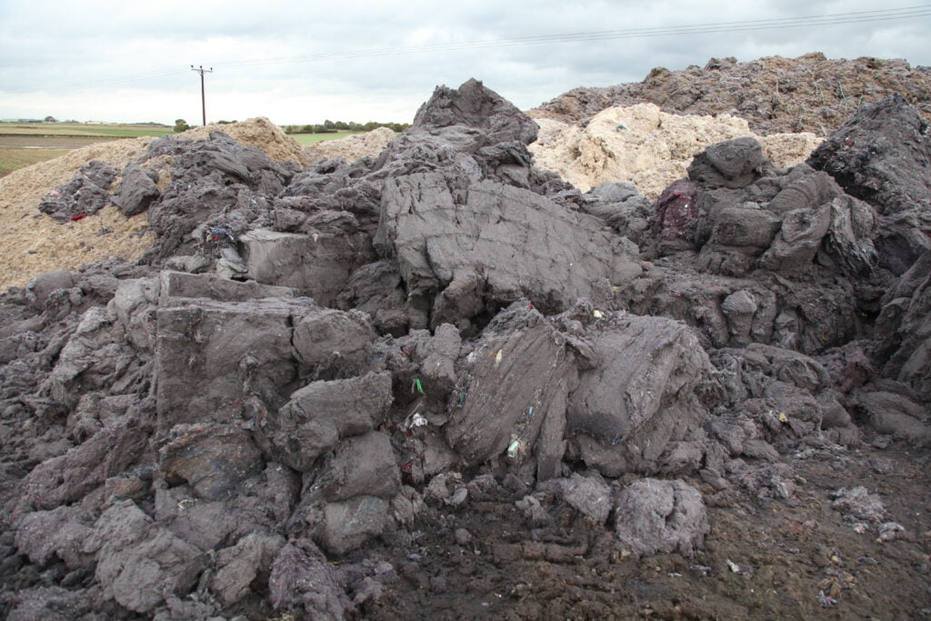 Pile of crumbling shoddy in the field, it looks like very compressed grey fluff.
