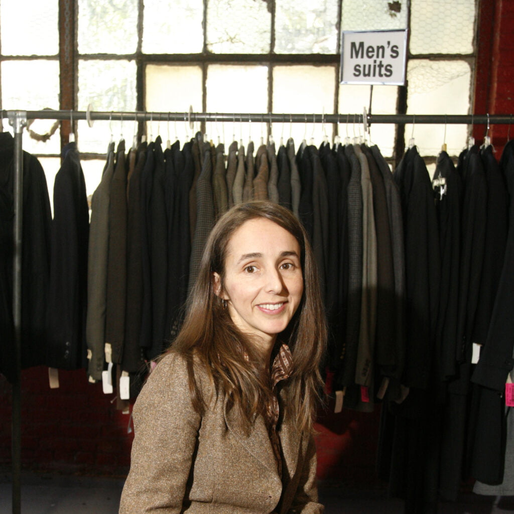 Photo of Hanna (who has brown hair, brown eyes, wearing a brown jacket and smiling)in front of a clothes rack of suits in front of a window, with the sign 'men's suits' in the upper right corner
