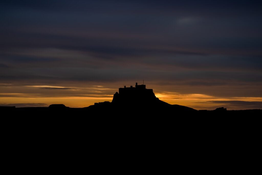 Silhouette of a castle on a hill against a sky during sunrise, going from a strip of bright yellow into a cloudy blue-grey.