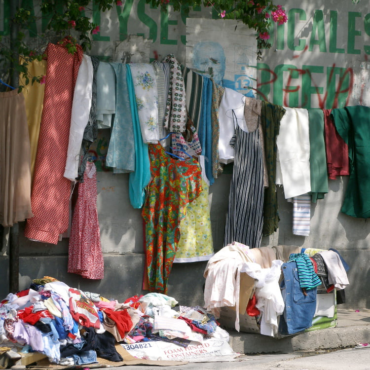 A wall of clothes hanging on a line, with piles on the ground and in a box. There is grafitti on the wall.