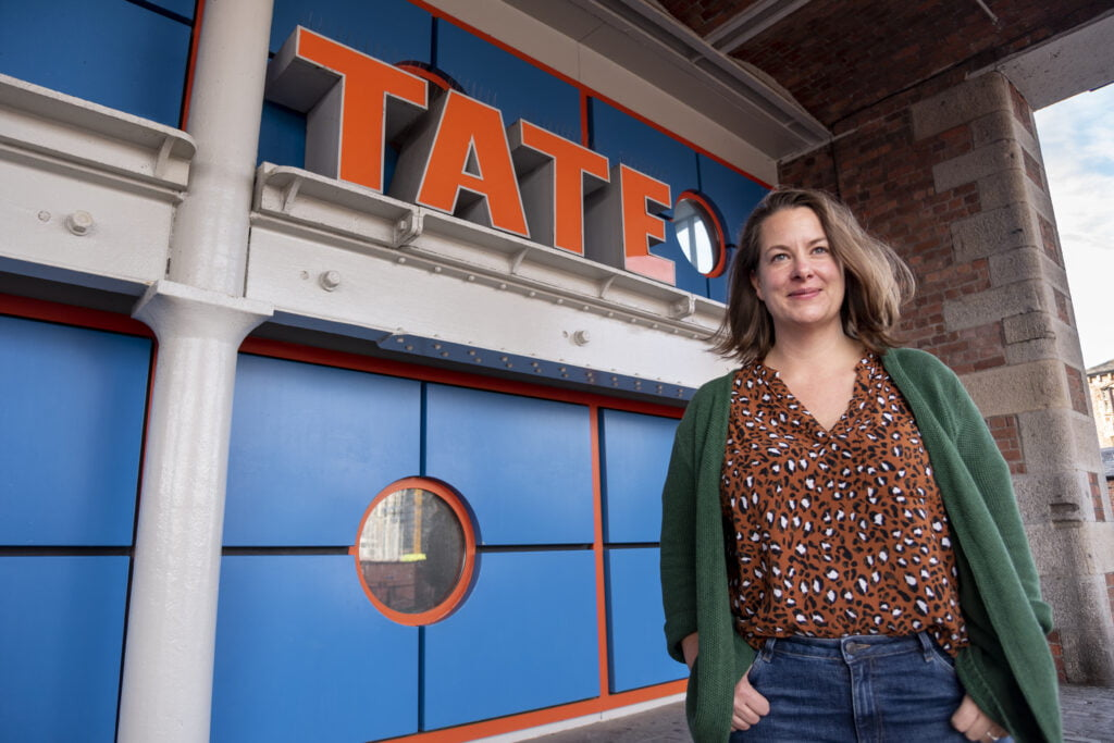 Portrait of Emily Speed outside the Tate Liverpool sign at the entrance. She is a white woman with medium length dark blond hair, wearing an animal print brown top, green cardigan and jeans