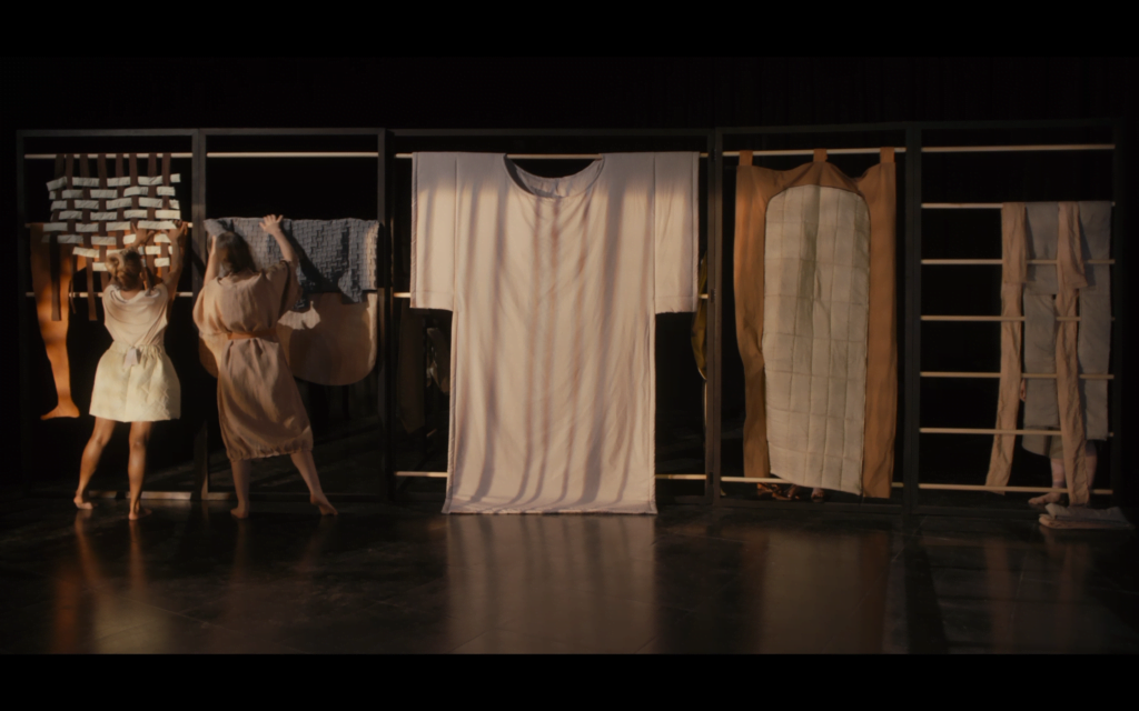 Film still from video shows performers interacting with textile pieces hung on a metal frame