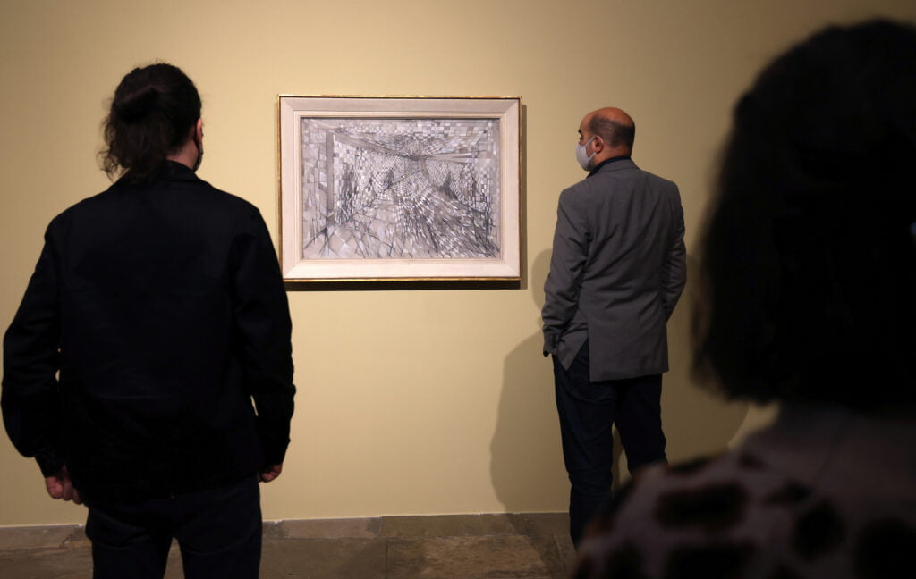 3 people seen from the back looking at a painting of an abstract black and white composition in a white and gold frame on a pale yellow wall.
