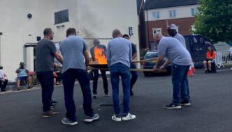 A group of men, dressed in blue trousers and long sleeved tops around a fire, ourtside a white building on the pavement, below a cloudy sky