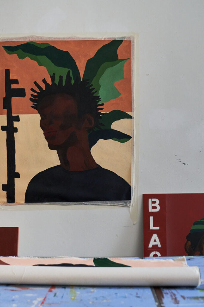Studio view of a painting in progress. The canvas is on the wall and depicts a black man with spiky hair and a leafy pattern in the background.