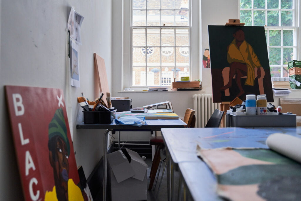 Artists studio with one painting on an easel, and another one propped against the wall. There are big windows and nautral light coming in, there is a table at the front with a painting in progress.
